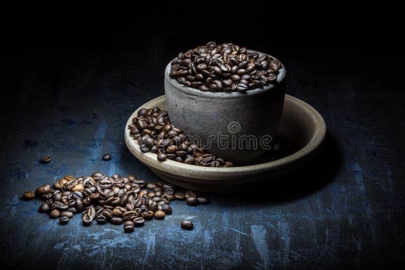 De kop van koffiebonen op donkere achtergrond stock foto