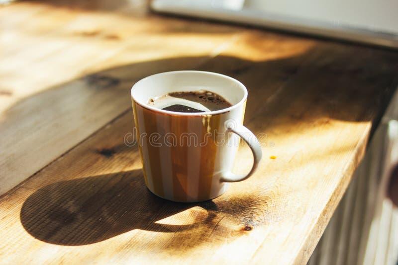 De kop van natuurlijke verse zwarte koffie in keuken, ochtend, hard licht stock afbeelding