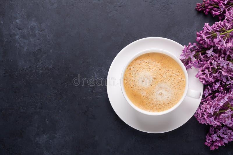 De kop van ochtendkoffie met de lente lilac bloemen vertakt zich tot bloei komend op zwarte steenachtergrond stock foto's