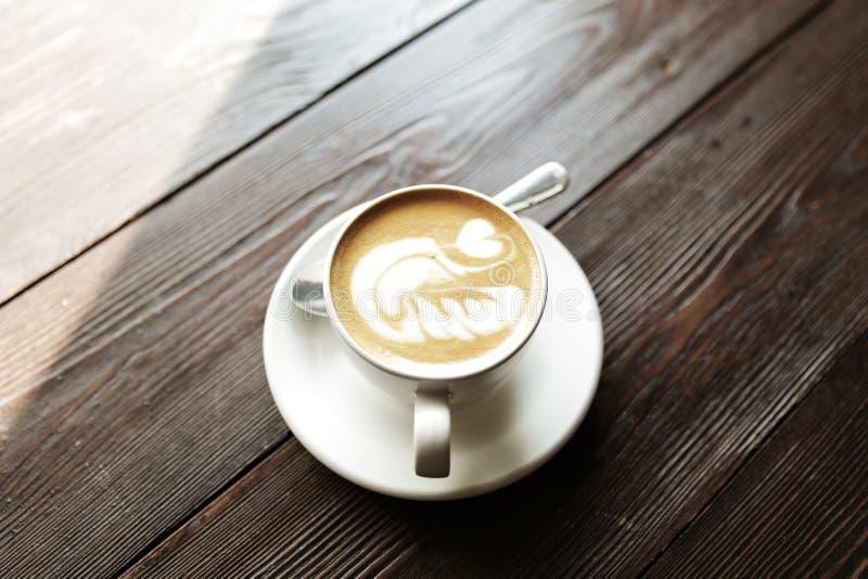 De kop van smakelijke latte bevindt zich op de houten geweven lijst royalty-vrije stock fotografie