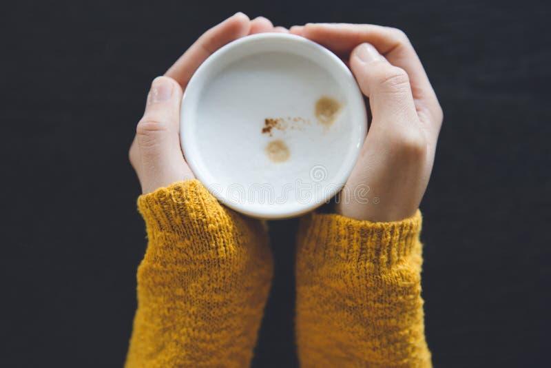 De kop van de vrouwenholding van hete koffie op donkere houten lijst royalty-vrije stock fotografie