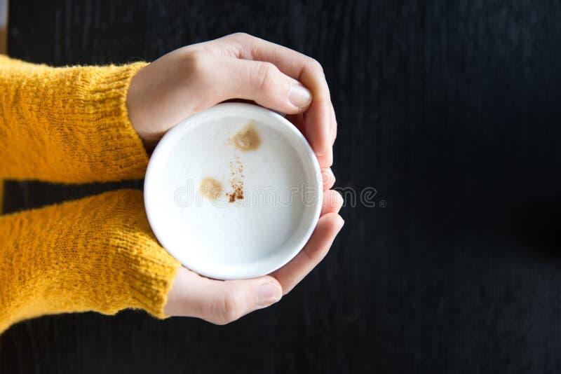 De kop van de vrouwenholding van hete koffie op donkere houten lijst royalty-vrije stock foto's