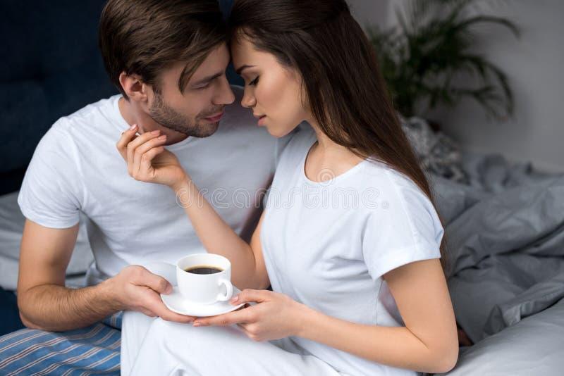De kop van de vrouwenholding van koffie en het omhelzen van haar echtgenoot terwijl royalty-vrije stock foto's