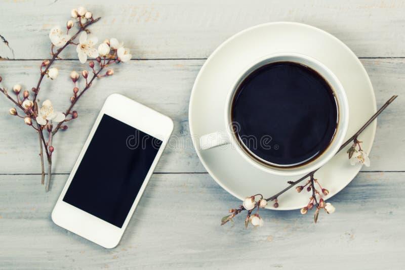 De kop van zwarte koffie en smartphone, op houten lijst met kers bloeit, hoogste mening, uitstekende filter stock afbeeldingen