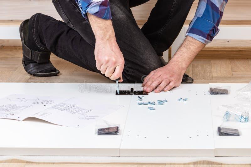 De koper verzamelt klaar-aan-assembleert het vouwen van lijst Klaar-aan-assembleer meubilair Installatie van huismeubilair stock afbeelding
