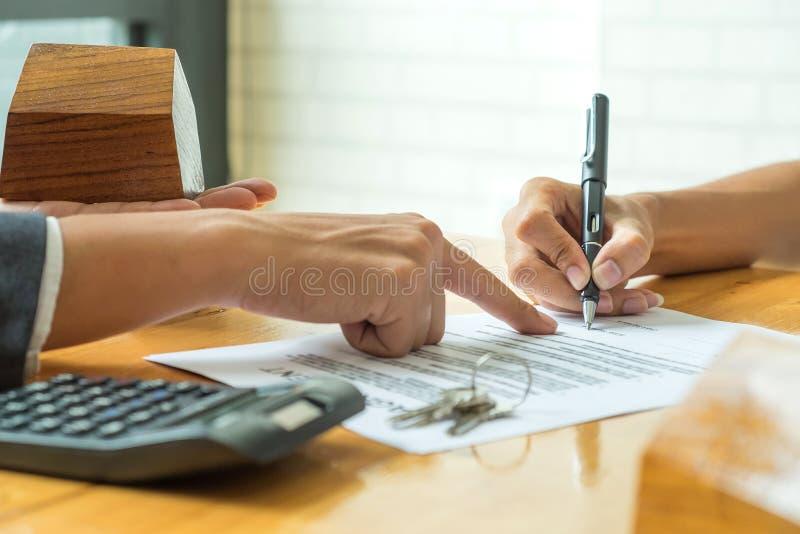 De kopers ondertekenen een overeenkomst van de huisaankoop van een makelaar royalty-vrije stock afbeelding