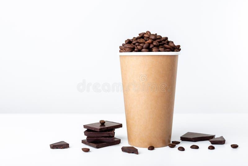 De kophoogtepunt van de ambachtkoffie van koffiebonen met chocolade op witte achtergrond royalty-vrije stock afbeeldingen