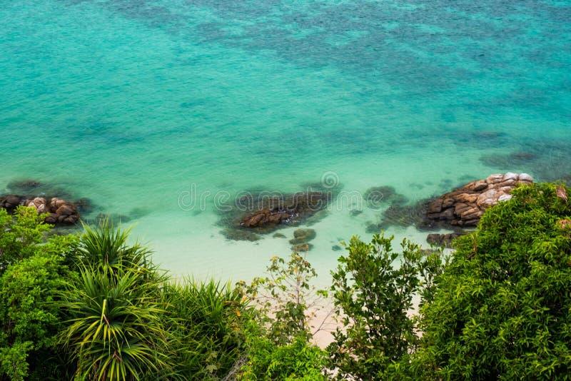 De koraalriffen langs het kust Turkooise water met groene struiken voor het overzees, golven maken de oppervlakte als smaragden d royalty-vrije stock afbeelding