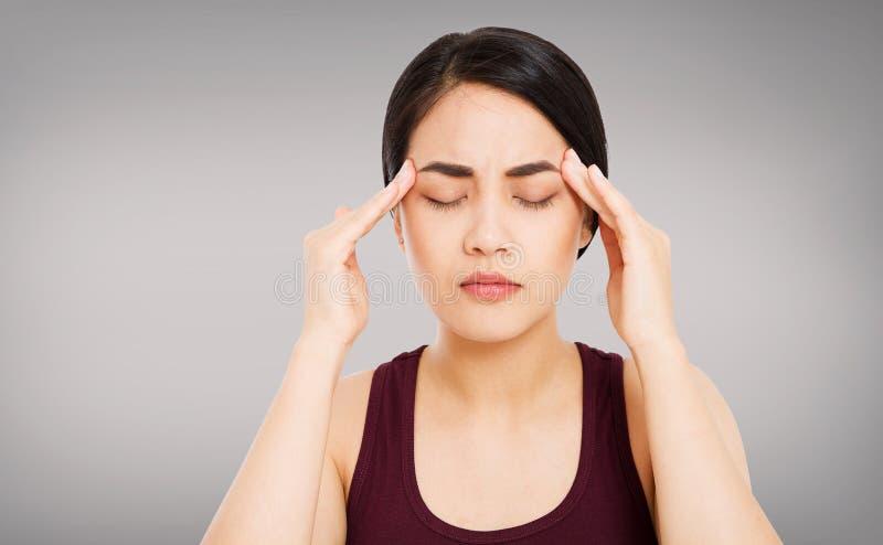 De Koreaanse vrouw met hoofdpijn, vrouwelijke migraine, lijdt hoofdpijn ge?soleerde grijze achtergrond van het vrouwen aan de Azi stock afbeelding