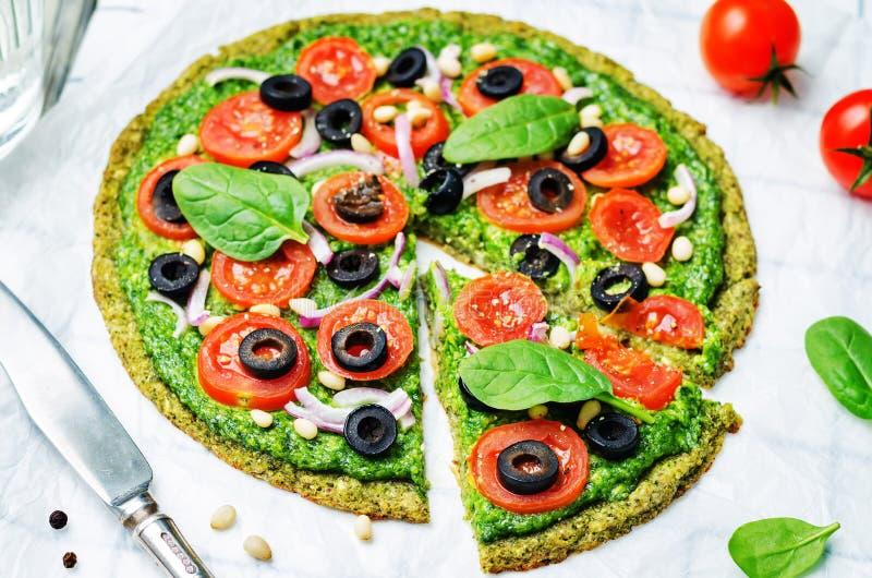 De korst van de de courgettepizza van veganistbroccoli met spinaziepesto, tomaten, ui en olijven royalty-vrije stock afbeelding