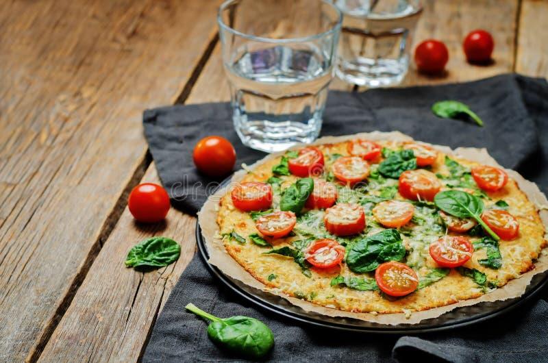 De korst van de bloemkoolpizza met tomaat en spinazie royalty-vrije stock foto's