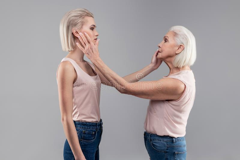 De kortharige ernstige vrouwen die elkaar inspecteren ziet onder ogen stock afbeelding