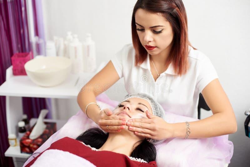 De kosmetiek arts die room op de gezichtsvrouw zetten royalty-vrije stock afbeeldingen