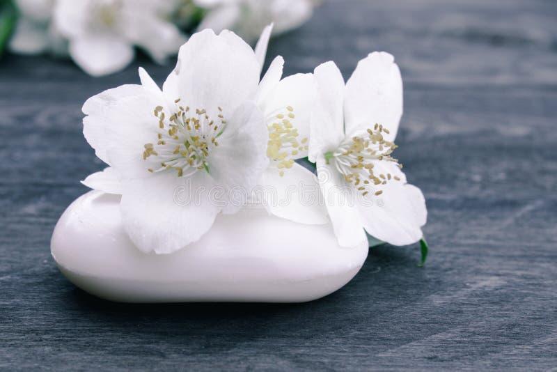 De kosmetische zeep en de witte jasmijnbloemen met groene bladeren liggen op een houten achtergrond Er is een plaats voor uw teks royalty-vrije stock afbeeldingen