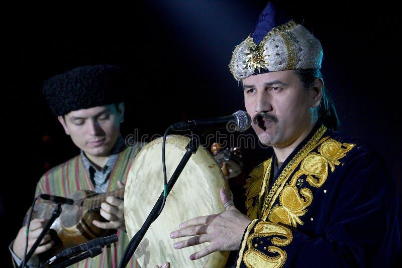 De kostuums die van Turkmeense Turkmenistan van de volksmuziekgroep nationale Oosterse mensen volksmuziek op volksinstrumenten sp stock foto's