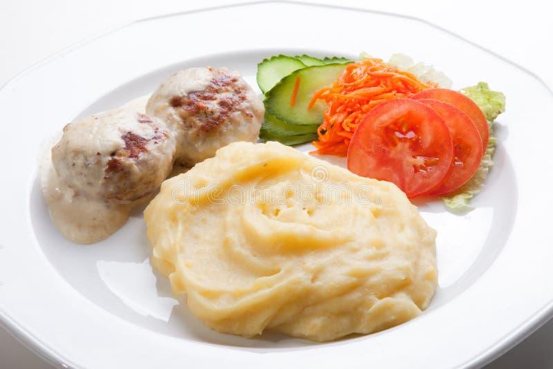 De kotelet van het vlees met fijngestampte aardappels en verse salade royalty-vrije stock afbeeldingen