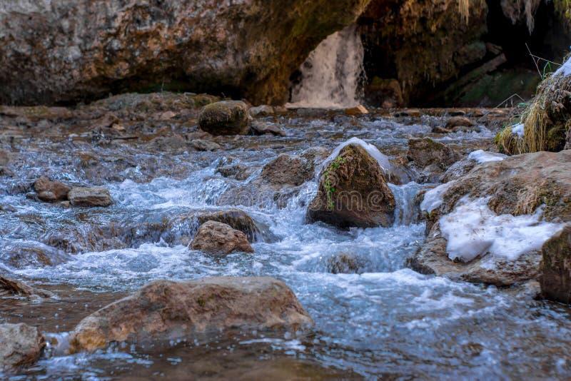 De koude bergrivier stroomt tussen stenen met sneeuw en ijs, selectieve nadruk, waterval op de achtergrond, karachay-Cherkess royalty-vrije stock foto's