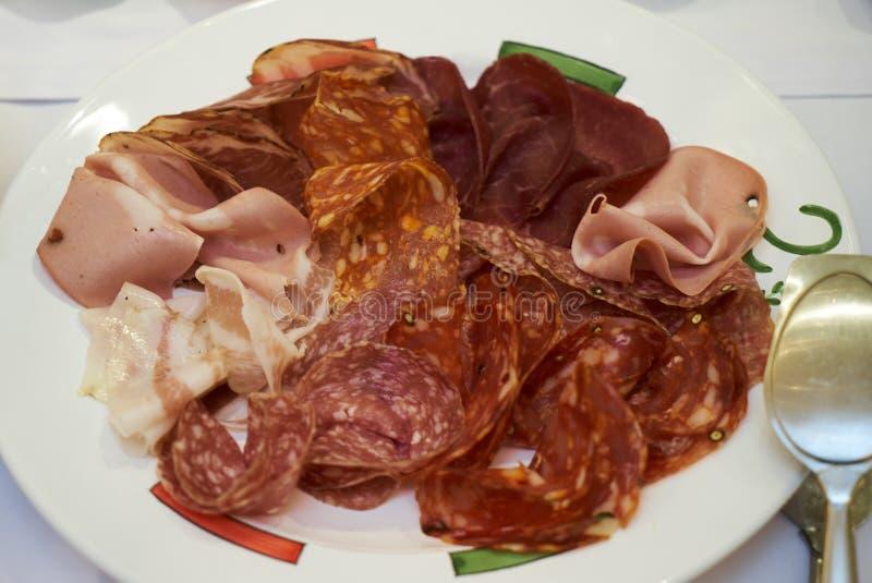 De koude rookte vleesplaat met gesneden varkensvlees, prosciutto, salami, ham royalty-vrije stock afbeeldingen