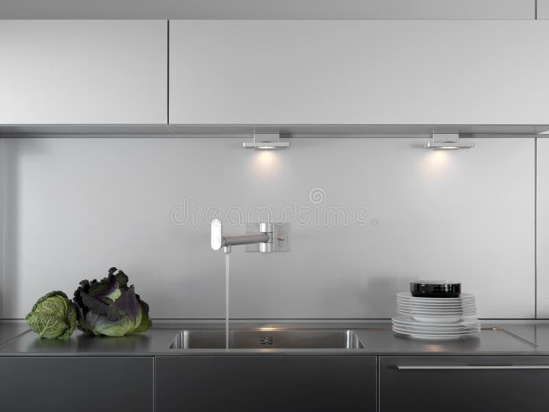 De kraan en de schotels van het water in een moderne keuken royalty-vrije stock foto