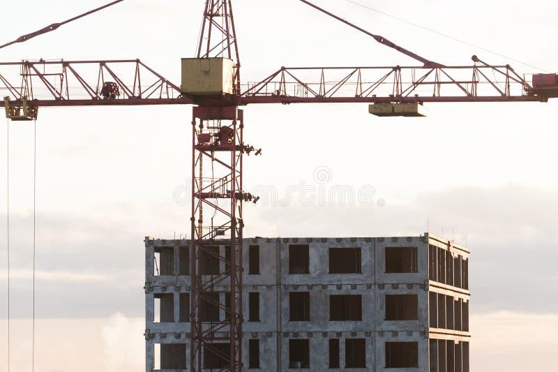 De kraan van de bouw dichtbij het gebouw in aanbouw stock afbeeldingen