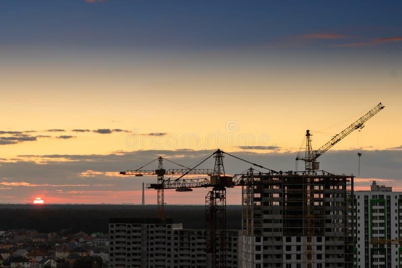 De kraan van de bouwtoren, Industriële bouwkranen op de verbazende achtergrond van de zonsonderganghemel stock afbeelding