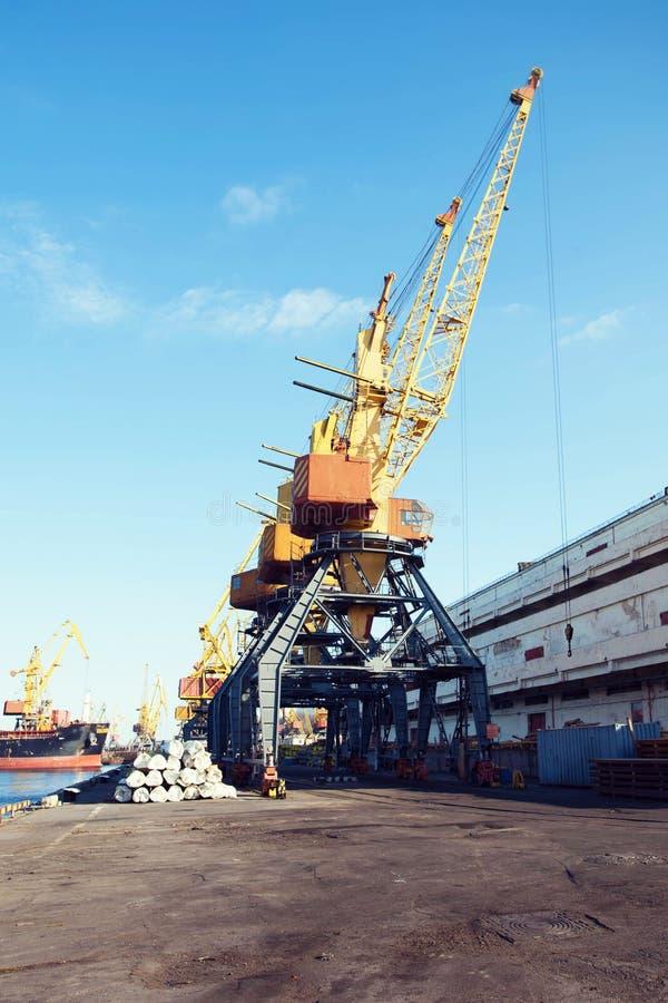De kraan van de havenlading over blauwe hemelachtergrond Zeehaven, kraan voor lading bij zonsondergang vervoer stock fotografie