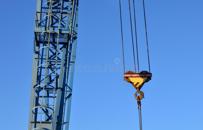 De kraan van de haakbrug op de ketting voor het opheffen van zware ladingen op de achtergrond van een metaalstraal en een blauwe  stock foto