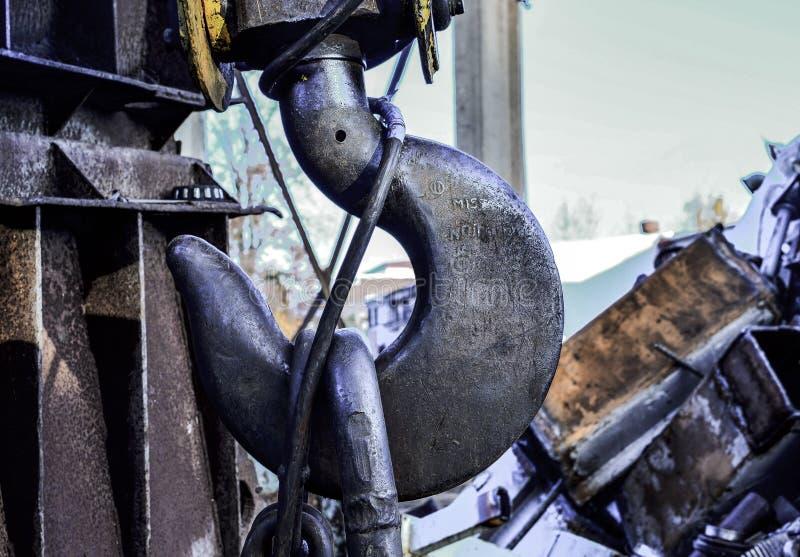 De kraan van de haakbrug op de ketting voor het opheffen van zware ladingen op de achtergrond van een metaalstraal en een blauwe  stock afbeelding