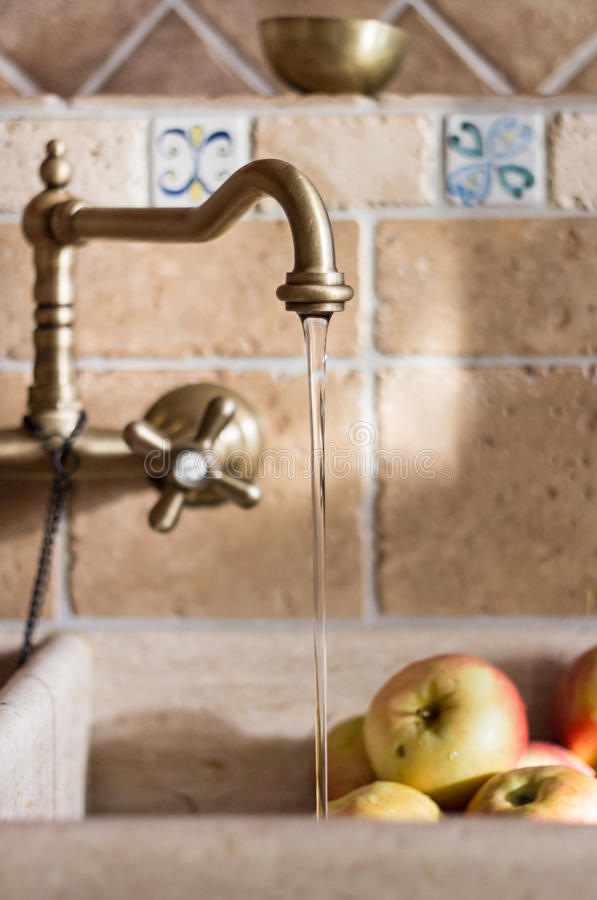 De kraan van het messingswater en de gootsteen van de granietkeuken stock afbeeldingen