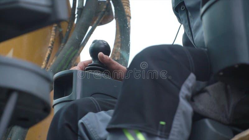De kraan van de ingenieursexploitant in actie klem De mens in cabine controleert de kraan Hij zit een bovenkant in kraan cabine e royalty-vrije stock foto's