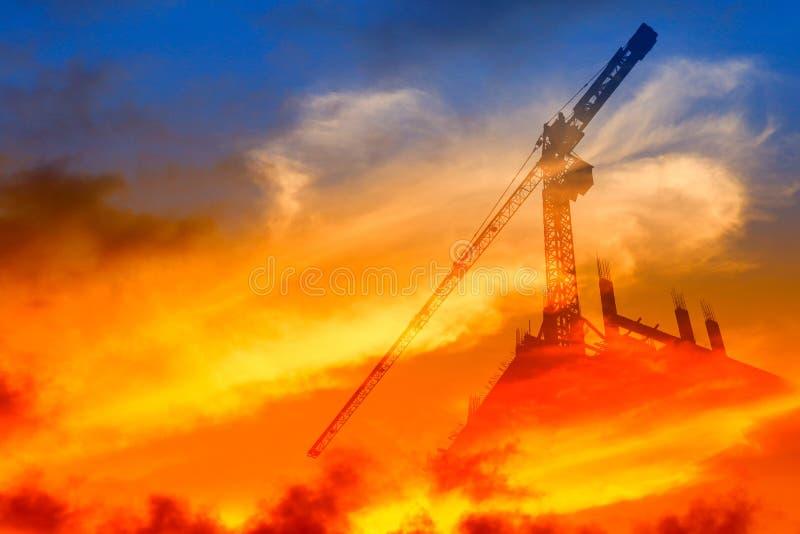 De de kraanbouwwerkzaamheid van de silhouettoren op de achtergrond van de zonsondergangtijd en de exemplaarruimte voegen de dubbe royalty-vrije stock afbeelding