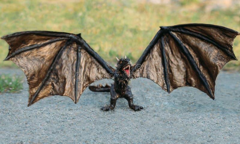 De krachtige sterke draak met zwarte dikke schalen, een mythisch sprookjeschepsel opende zijn mond voor collage, het bang maken stock afbeeldingen