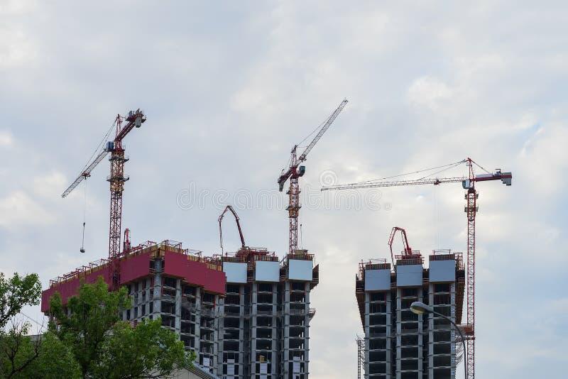 De kranen van de lifttoren op bouwwerf tegen achtergrond van de blauwe hemel, huizen nieuwe gebouwen dichtbij een woonwijk stock afbeelding