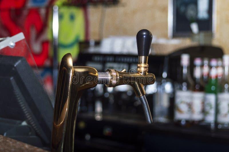 De kranen van het koperbier in een donkere bar stock afbeelding