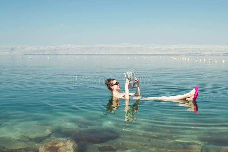 De krant die van de meisjeslezing op oppervlakte Dode Overzees drijven geniet de zomer van zon en vakantie Recreatietoerisme, gez stock fotografie