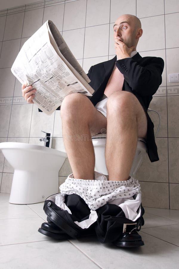 De krant van de lezing op toilet royalty-vrije stock foto's