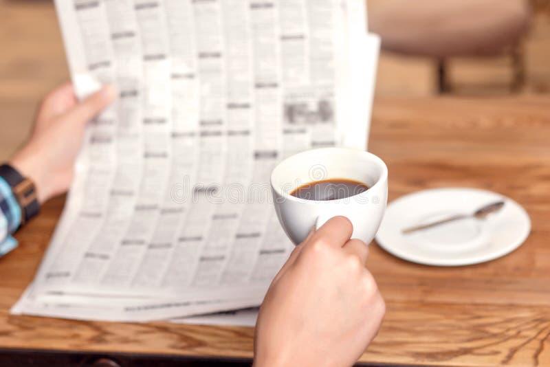 De krant van de mensenlezing en het drinken koffie stock afbeelding