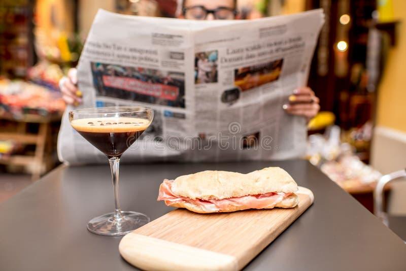 De krant van de vrouwenlezing bij de koffie in openlucht stock afbeeldingen