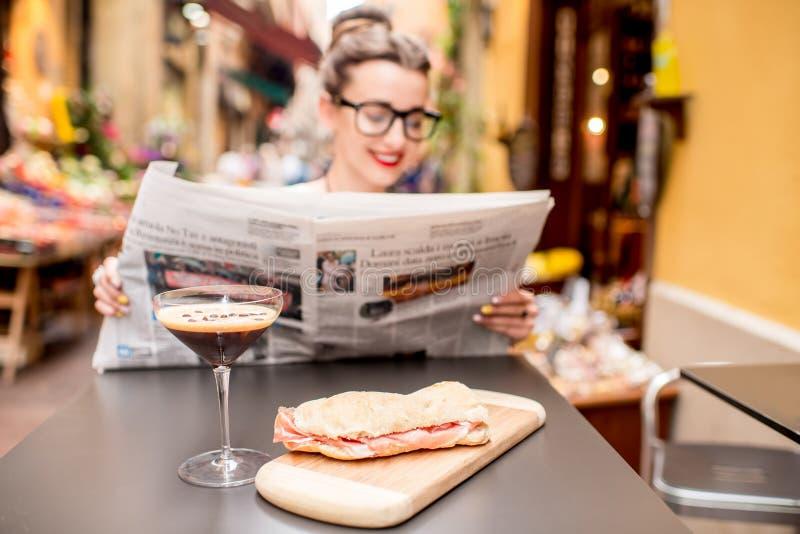 De krant van de vrouwenlezing bij de koffie in openlucht stock foto's