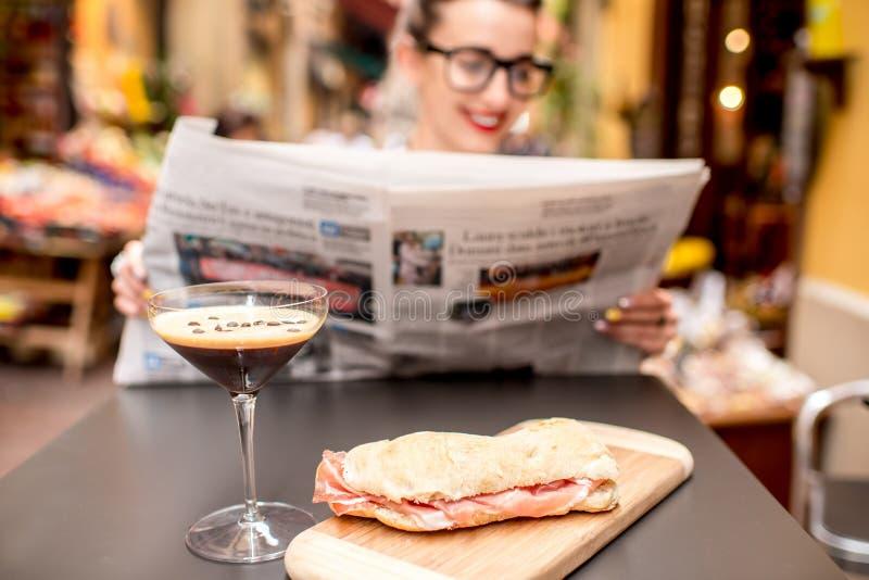 De krant van de vrouwenlezing bij de koffie in openlucht royalty-vrije stock foto
