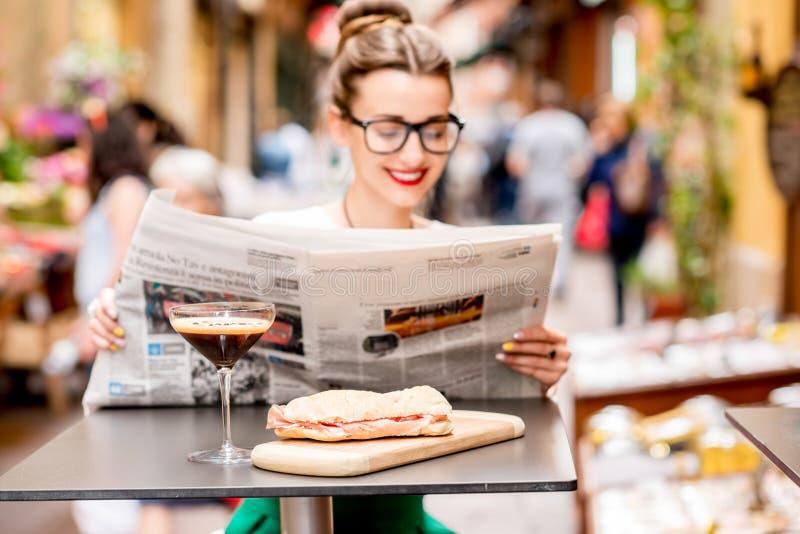 De krant van de vrouwenlezing bij de koffie in openlucht stock fotografie