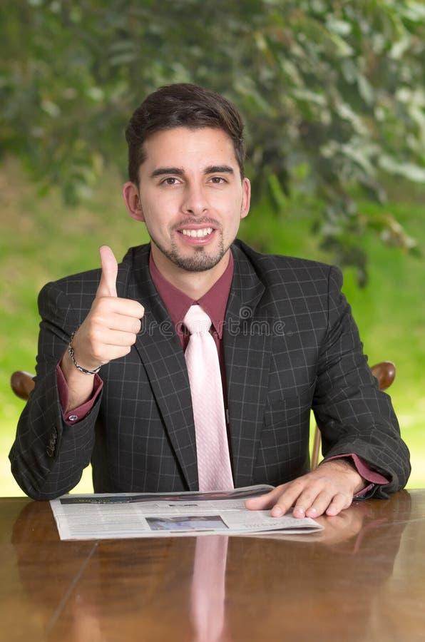 De krant van de zakenmanlezing met omhoog duimen, stock foto