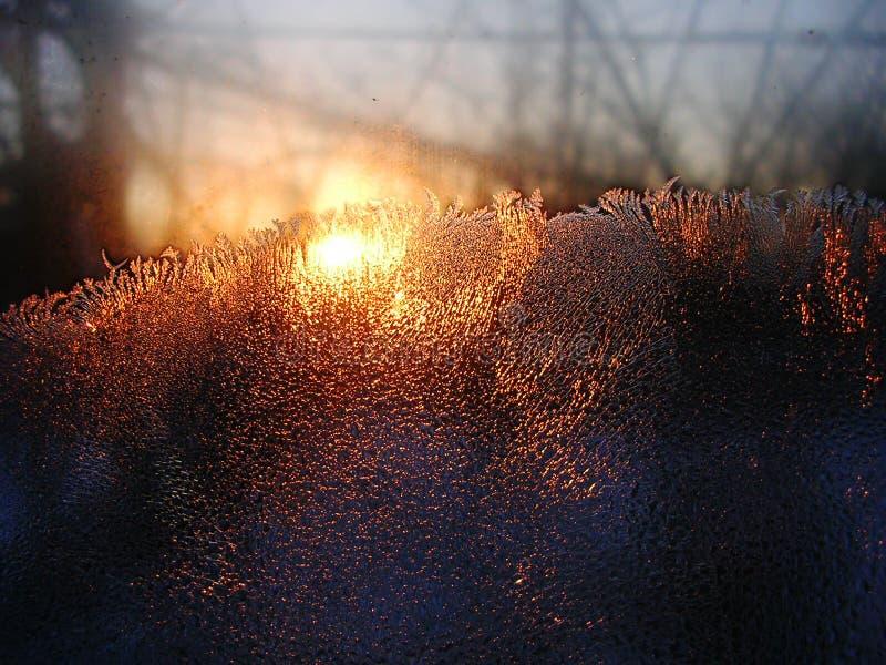 De kristallen van het vorstijs en waterdalingen op vensterglas op de achtergrond van zonsopgang royalty-vrije stock fotografie