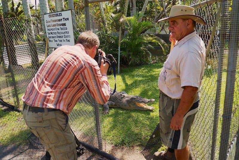 De krokodillandbouwer Mick Tabone opent pen voor een niet geïdentificeerde toerist om een foto van een zoetwaterkrokodil in Jonst royalty-vrije stock afbeelding