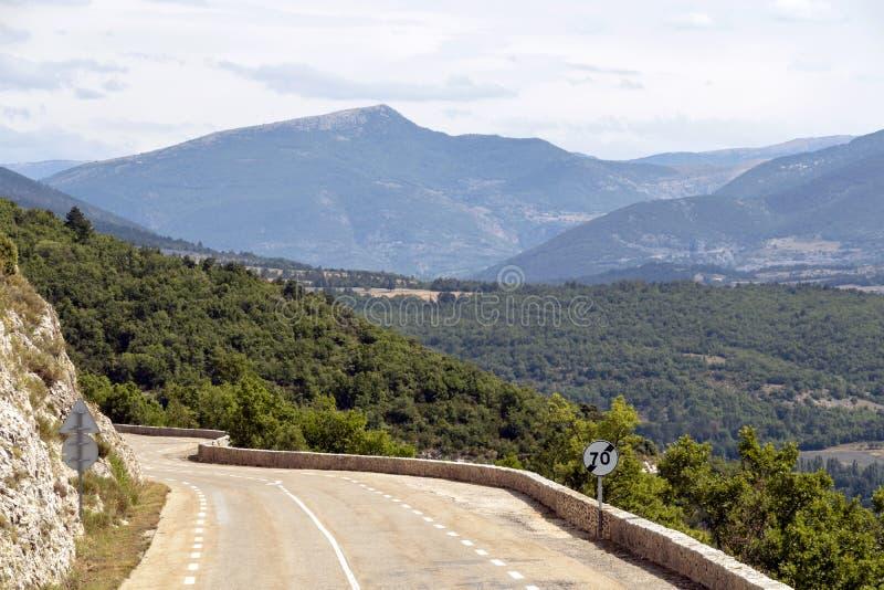 De kromme van de bergweg boven de bos en landbouwgebieden in Frans platteland stock afbeeldingen