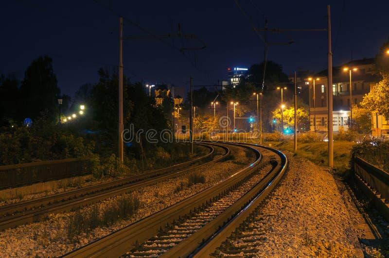 De kromme van het spoorwegspoor bij nacht in de stad stock afbeeldingen