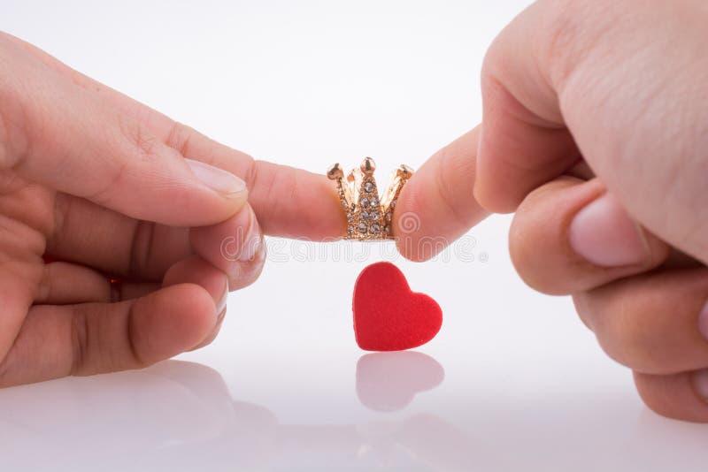 De kroon van de handholding dichtbij een hart royalty-vrije stock afbeelding