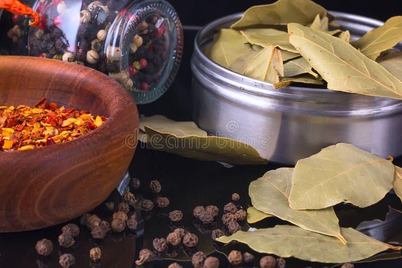 De kruiden en de kruiden, het laurierblad, de zwarte peper en de houten kom van Spaanse peper schilferen af stock afbeelding
