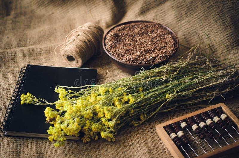 De kruiden en de zaden liggen op de lijst naast het notitieboekje en het houten telraam Uitstekende rustieke stijl Zachte nadruk stock foto