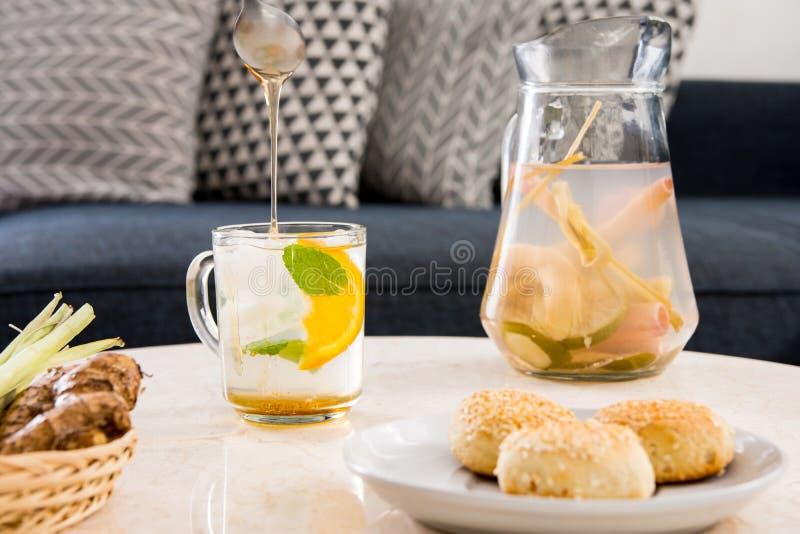 De kruidengember en citroengrasthee diende met munt, honing en een plak van sinaasappel stock foto